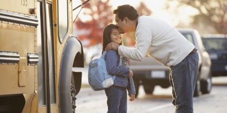 Father kissing daughter goodbye in front of school bus